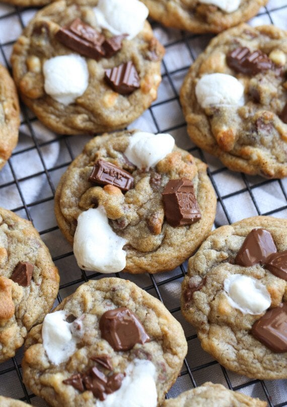 S'mores cookies on a wire rack topped with melted marshmallows and milk chocolate
