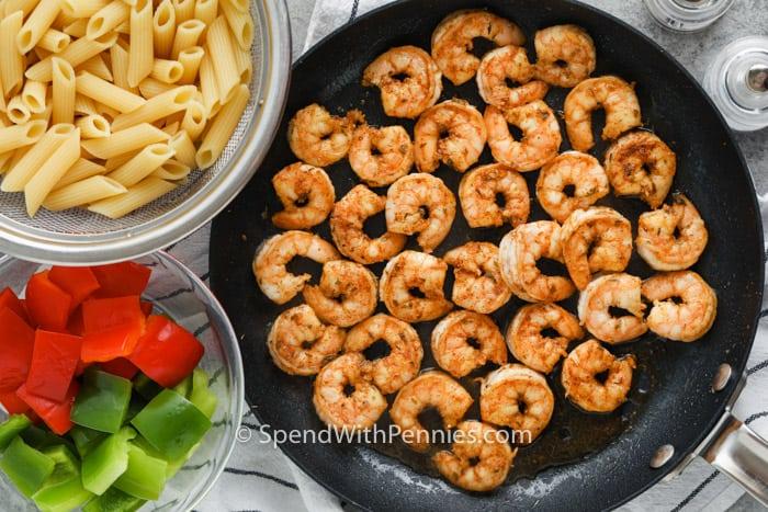 főtt garnélarák az edényben, és tálak hozzávalói a Cajun garnélarák tészta elkészítéséhez
