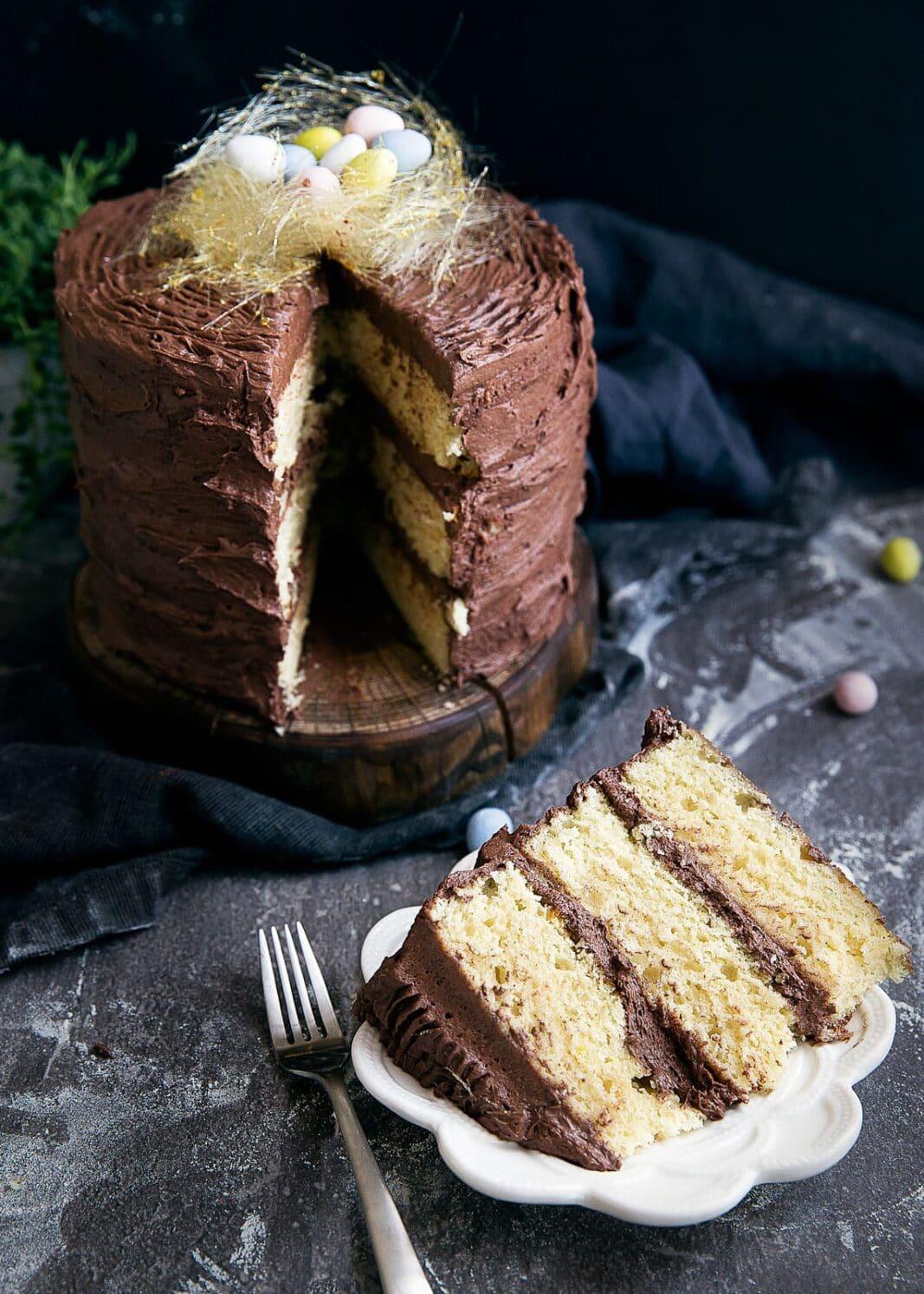 Nedves vaníliarétegű sütemény, csokoládé vajkrém és egy fonott cukormadárfészek teszi ezt a süteményt tökéletesen húsvétra!