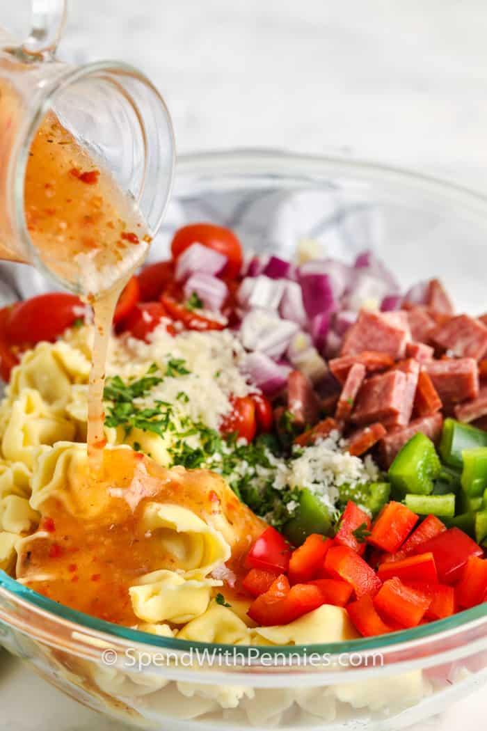 öntetet öntenek a legfelső összetevőkre az olasz Tortellini saláta elkészítéséhez