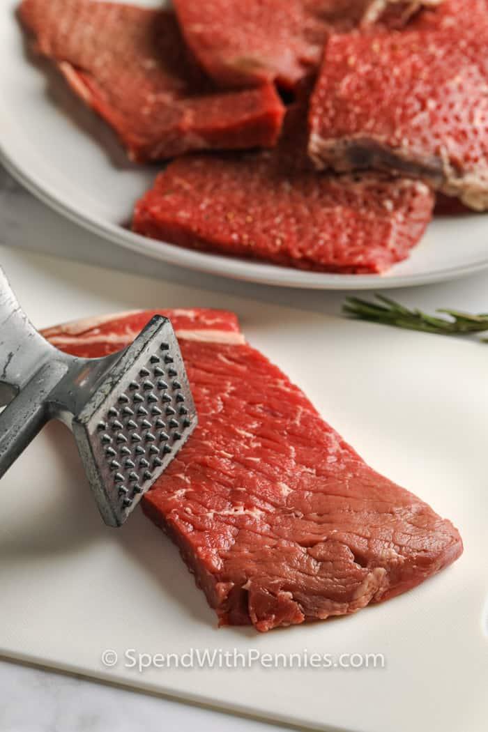 steak darabokat egy tányéron és vágódeszkán, hogy kerek steaket és gombát készítsen