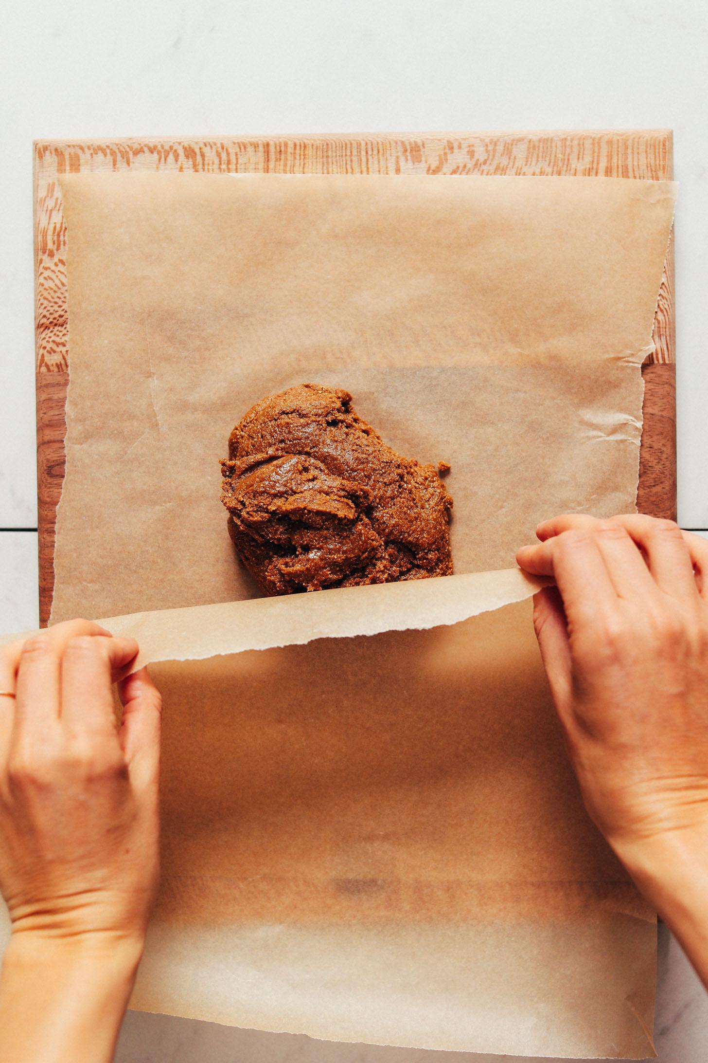 Sütőpapírt helyezünk egy gluténmentes graham krakkoló tészta gömbjére, hogy laposra gördüljön