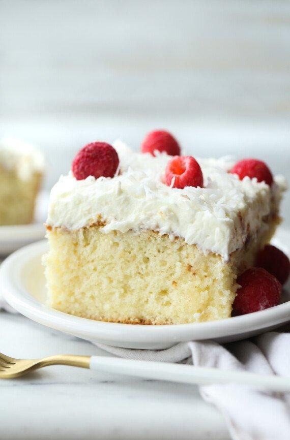 Szelet kókuszpiszkos sütemény egy tányéron, tetején habosított cukormázzal