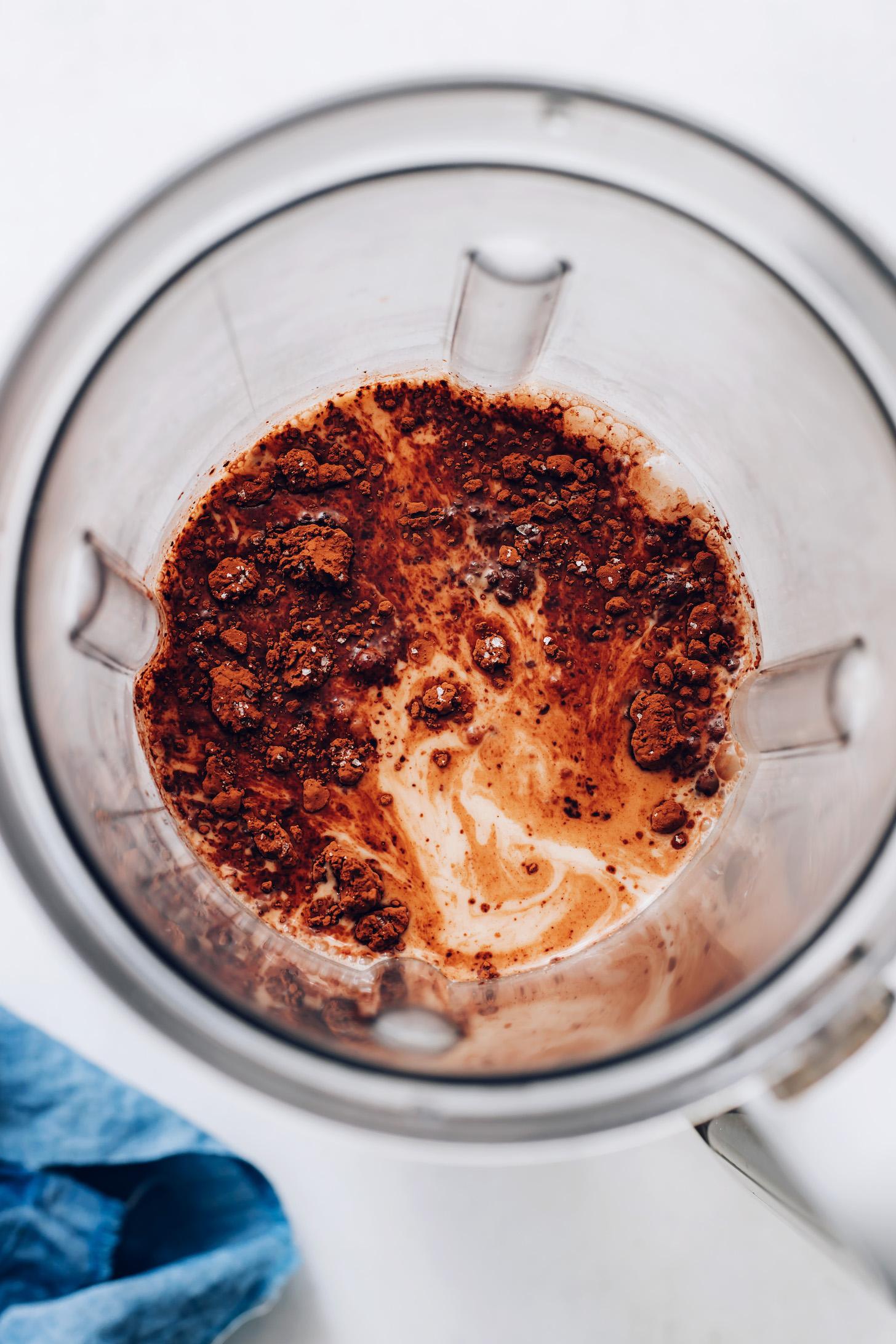 Turmixgép kakaóporral a tejszínes mogyorós tej fölött