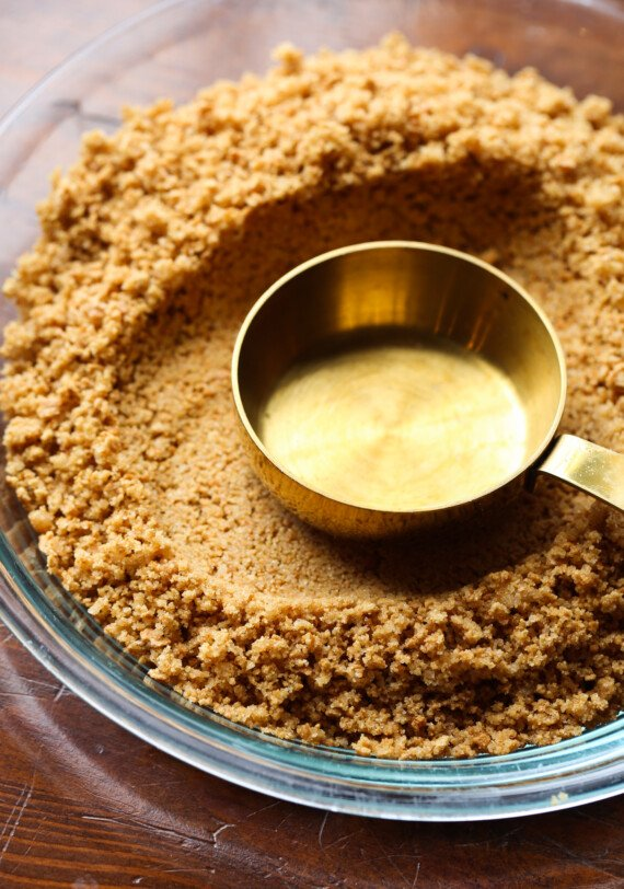 Measuring cup pressing into a graham cracker crust.