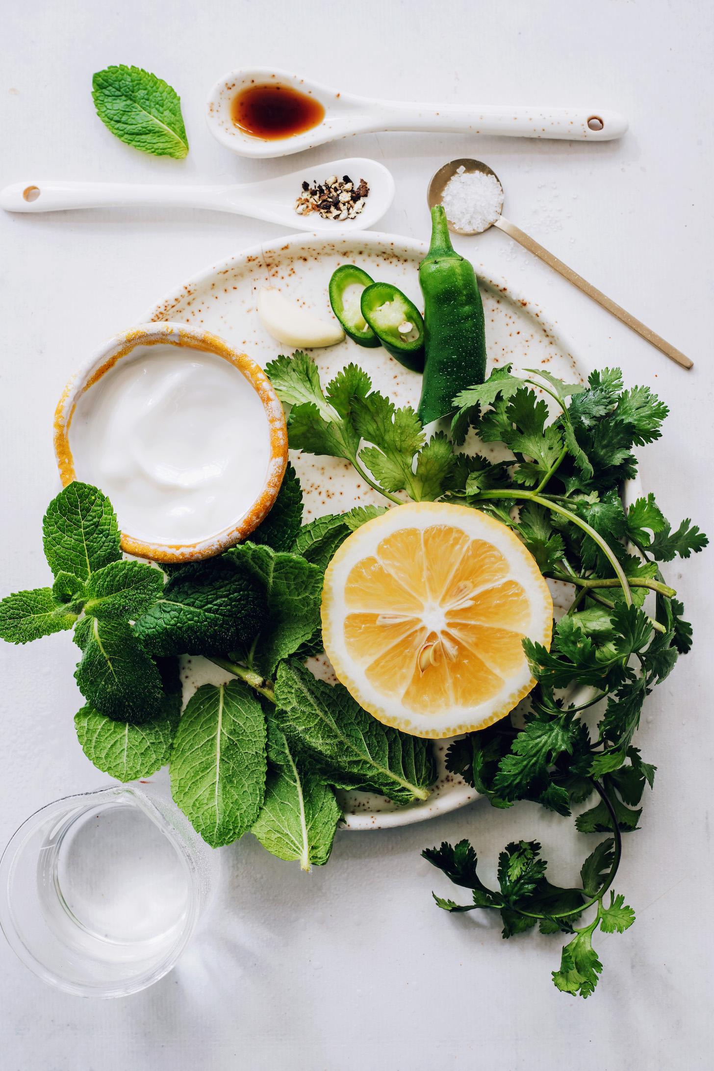 Juharszirup, só, bors és víz egy tányér körül kókuszjoghurttal, mentával, korianderrel, citrommal, jalapenóval és fokhagymával