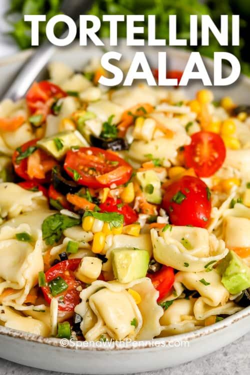 Tortellini saláta egy tálba egy kanállal és írás