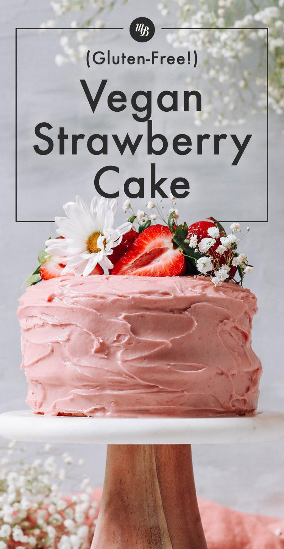 Vegán és gluténmentes epres torta süteményes tányéron, friss eperrel és virággal a tetején