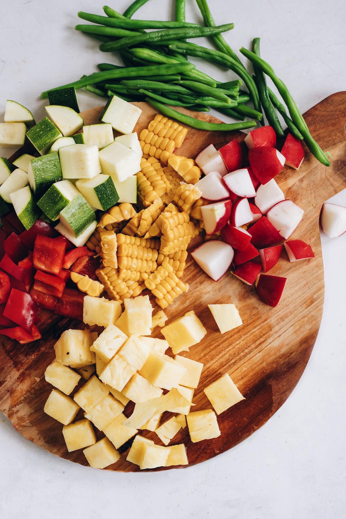Vágódeszka friss zöldbabbal, cukkini, piros kaliforniai paprika, kukorica, retek és ananász