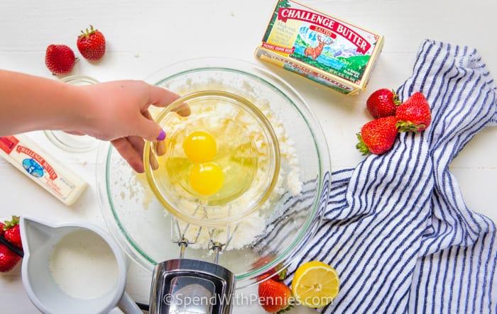 tojást adva a tálba eper kenyér elkészítéséhez