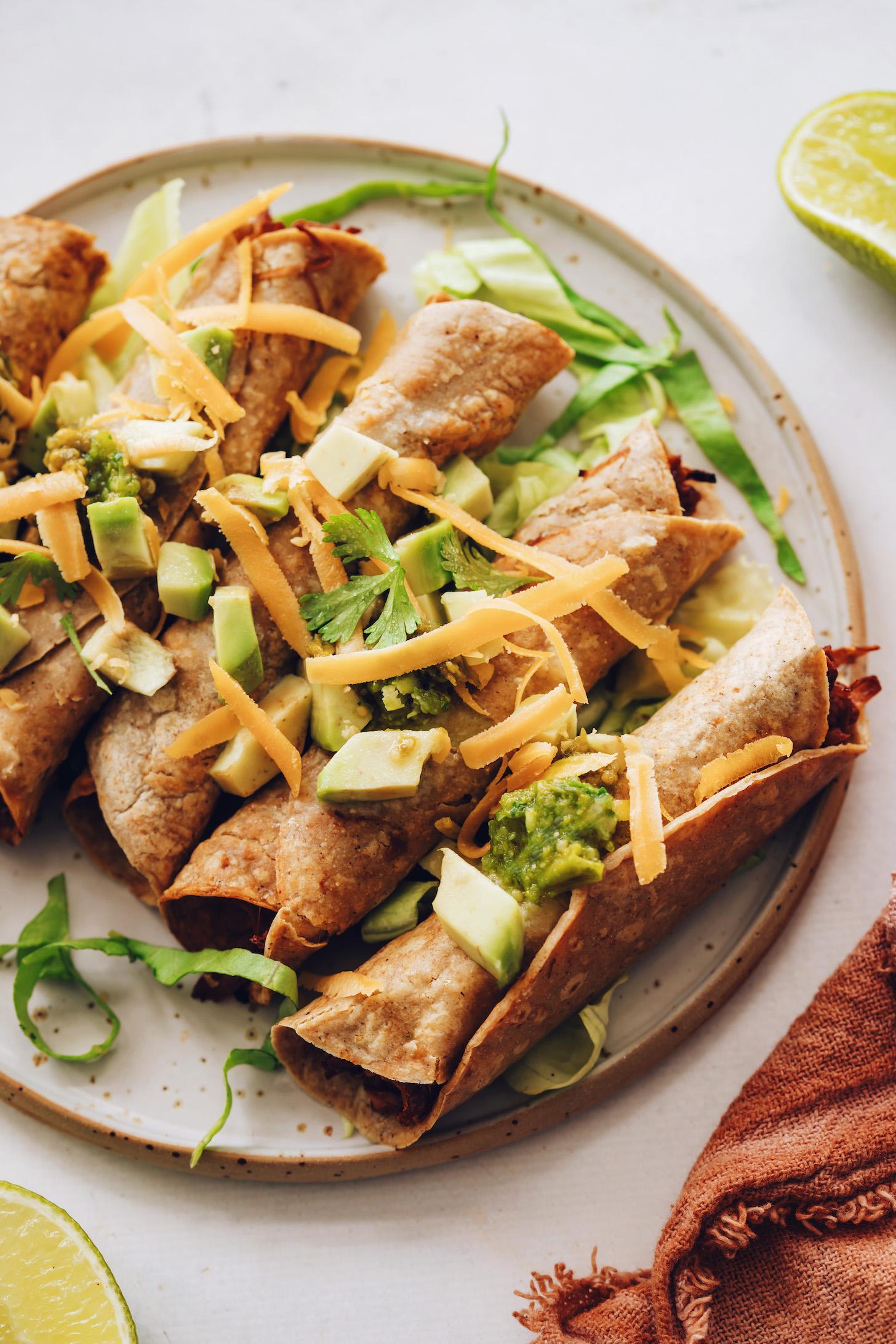 Tányér jackfruit taquitos avokádóval, korianderrel, salátával, vegán cheddarral és tomatillo salsa -val