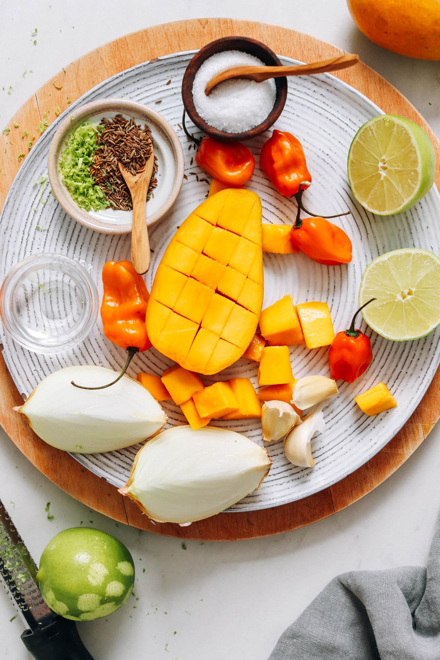 Tányér sóval, limmel, habaneróval, mangóval, köménymaggal, limehéjjal, vízzel, hagymával és fokhagymával