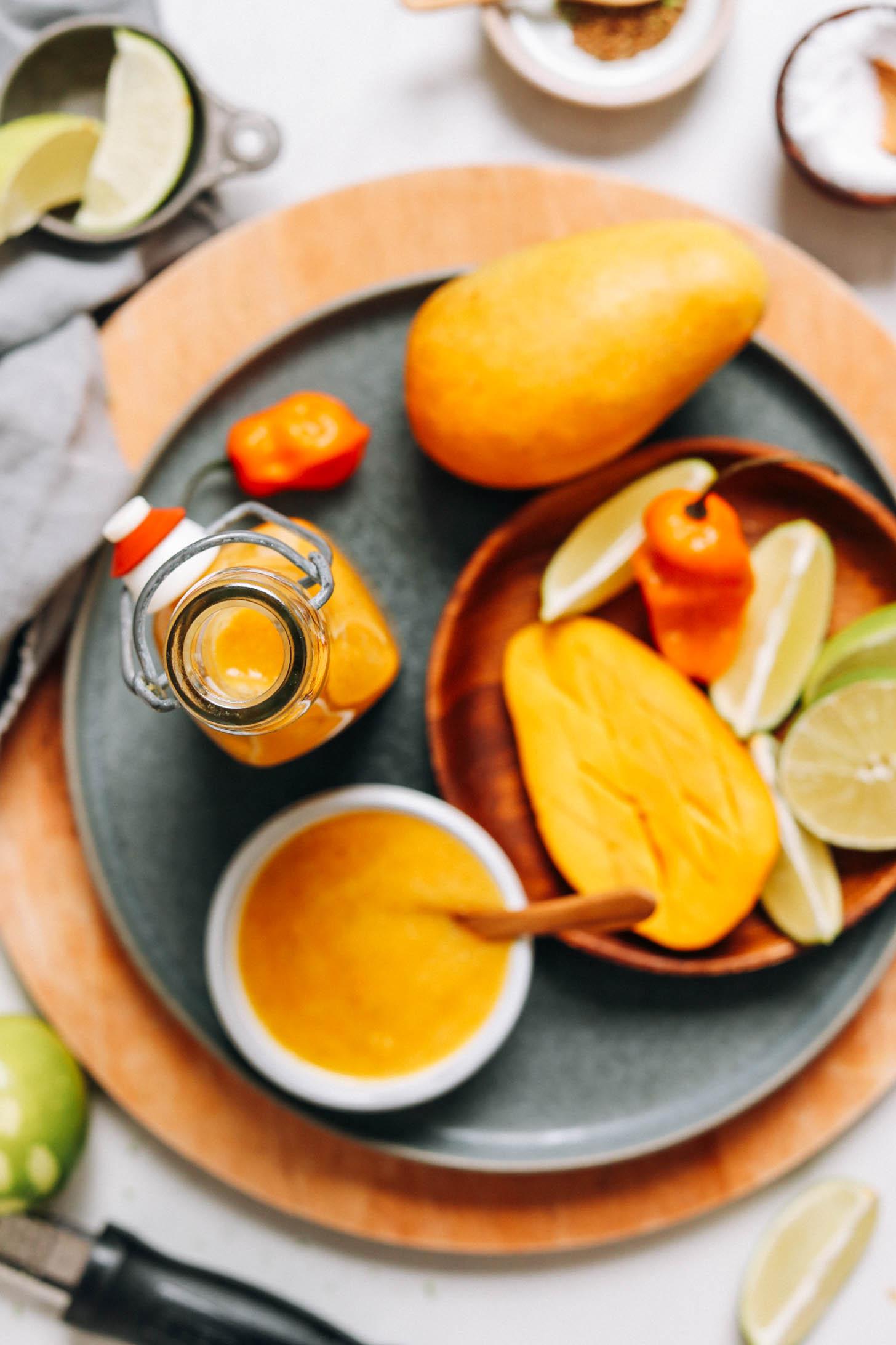 Üveg és tál mangó habanero forró mártással az elkészítéshez használt hozzávalók mellett