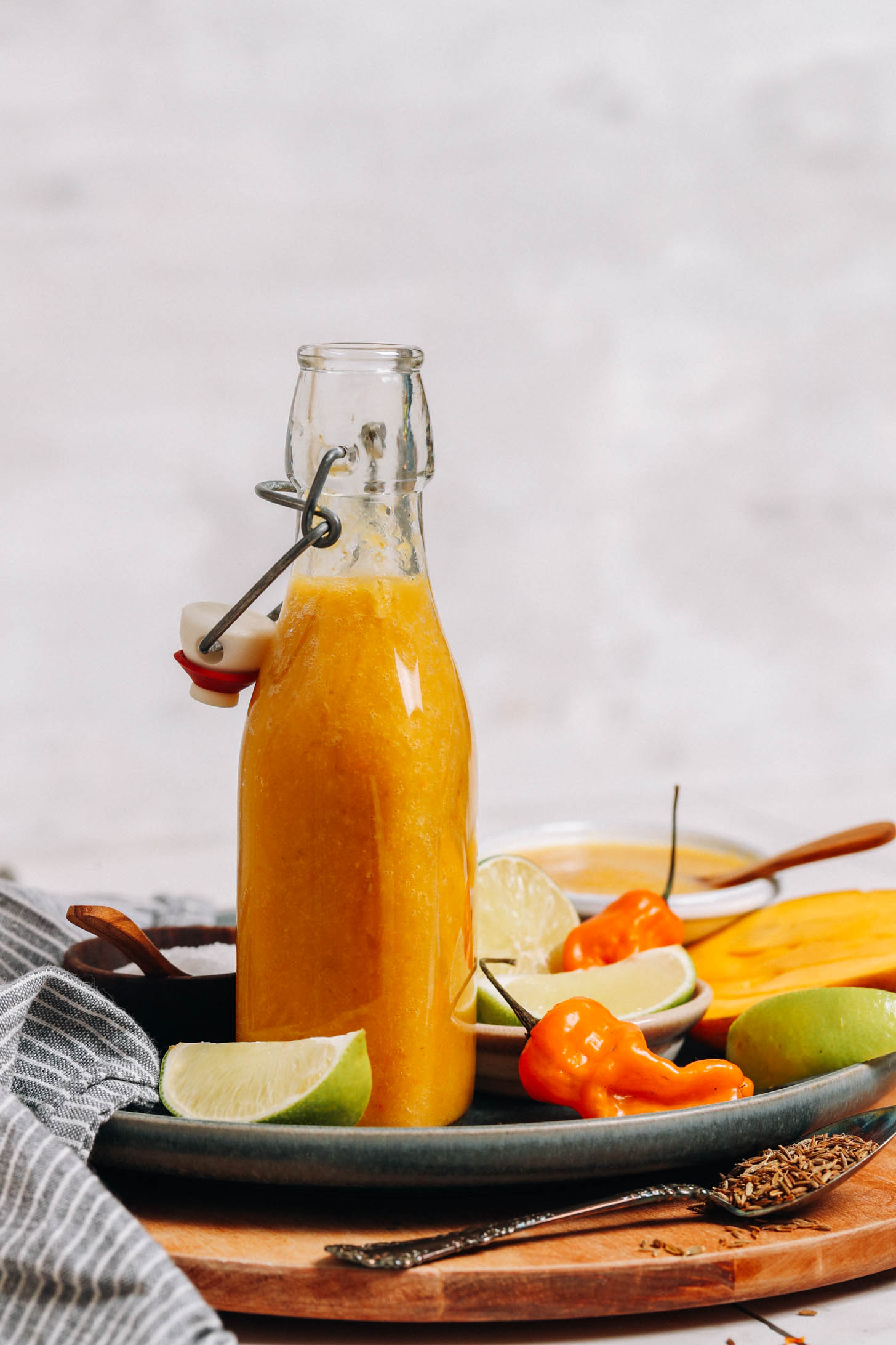 Nyisson ki egy üveg házi habanero forró mártást egy tányérra az elkészítéshez használt összetevőkkel